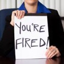 Woman holding up 'You're FIRED!' poster